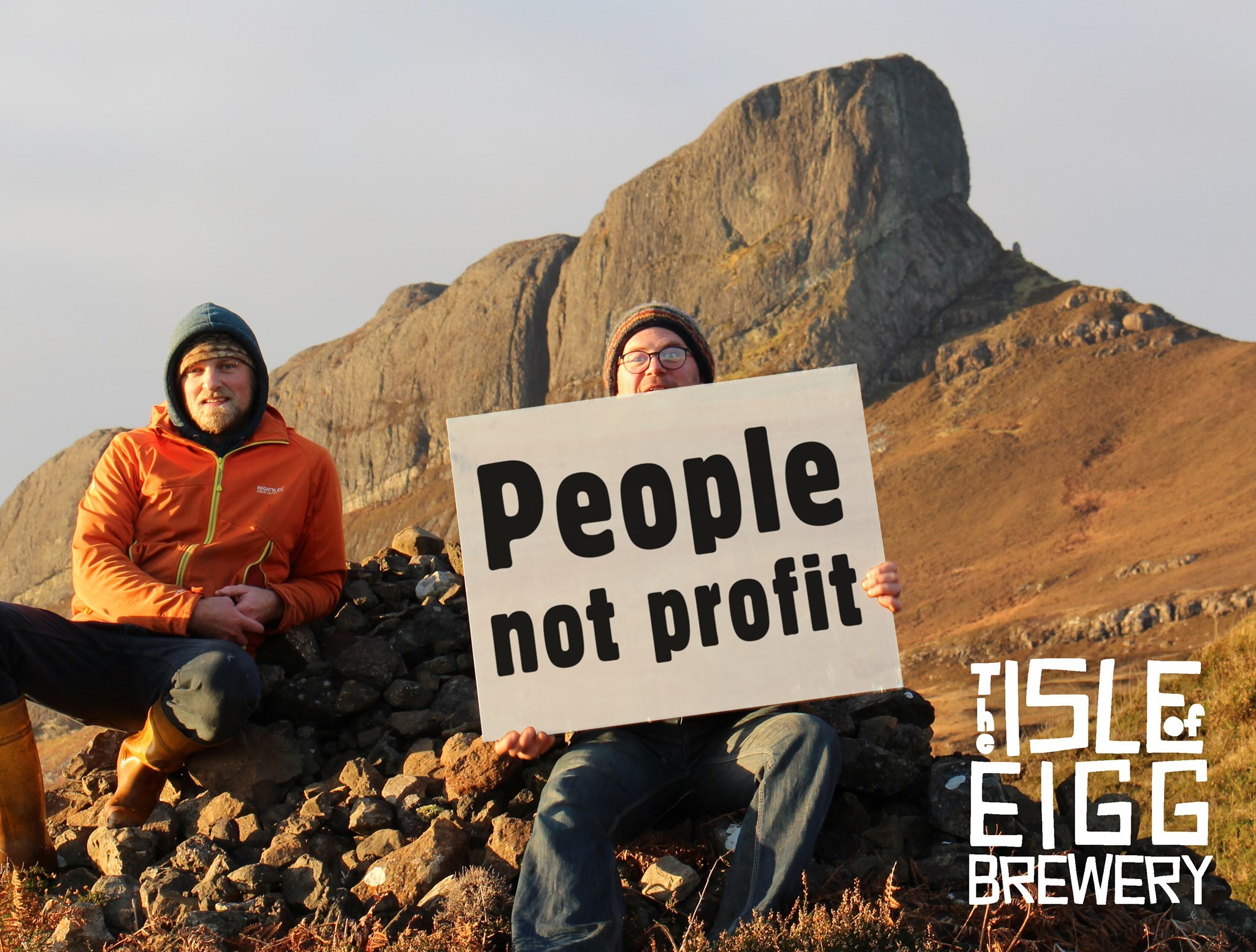 """Founding members of Isle of Eigg Brewery pose before Sgurr, the island's highest peak, with a sign reading """"People not Profit"""""""